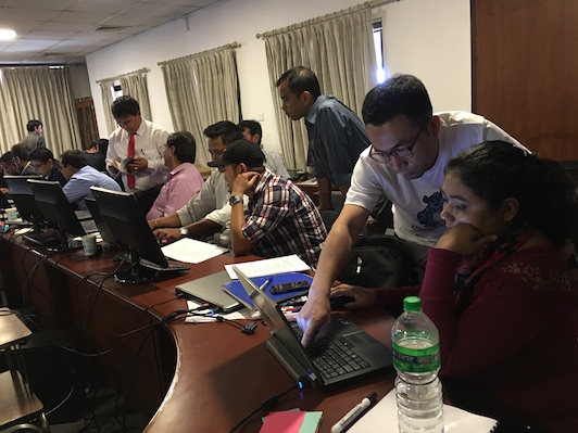 Trainers and trainees working on laptops during hands-on session