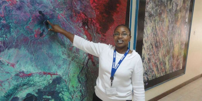 Photo of RCMRD's Anastasia Wahome pointing at map